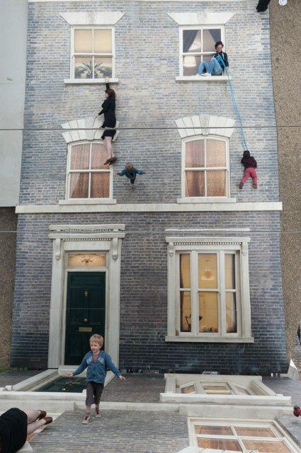 Iluzie vizuala: O cladire inalta si membrii unei familii atarnati la f - Poza 1