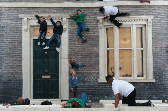 Iluzie vizuala: O cladire inalta si membrii unei familii care atarna la ferestre